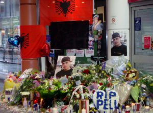 A candle-encircled shrine of flags, photos, and flowers to Zekaj's memory has been set up outside the Mall, where several Albanian males have been keeping vigil.