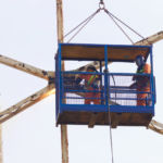 The cage hanging from the crane containing the workmen